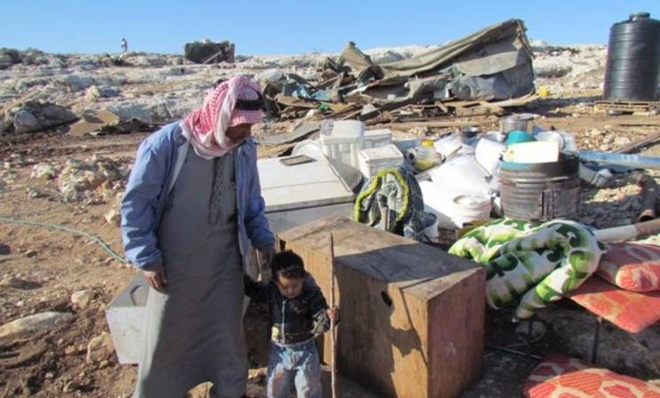 """Father and child amongst their belongings following the demolition."""