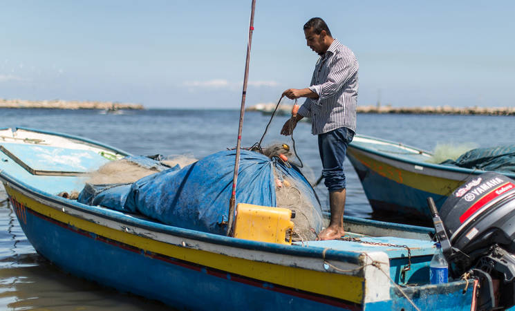 "Fisherman Amjad al-Shirafi is preparing his boat at the Gaza seaport. ""All I wish is to live my life with my family in dignity and to be able to sail like other fishermen in the world,"" he said. © 2016 UNRWA Photo by Tamer Hamam."