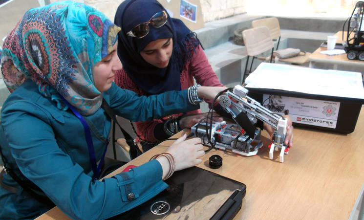 10th grade UNRWA students Bayan Ali and Hadeel Al-Hayek, from Al-Jofeh Preparatory Girls' School, work on an industrial pick and place robot. © UNRWA
