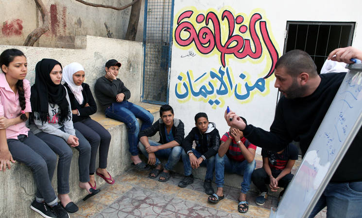 Mohammad, an UNRWA volunteer, engages young Palestine refugees at the Haifa School Collective Centre in Damascus to prevent gender-based violence, as part of the US-funded 'Safe from the Start' initiative. © 2016 UNRWA Photo by Taghrid Mohammad