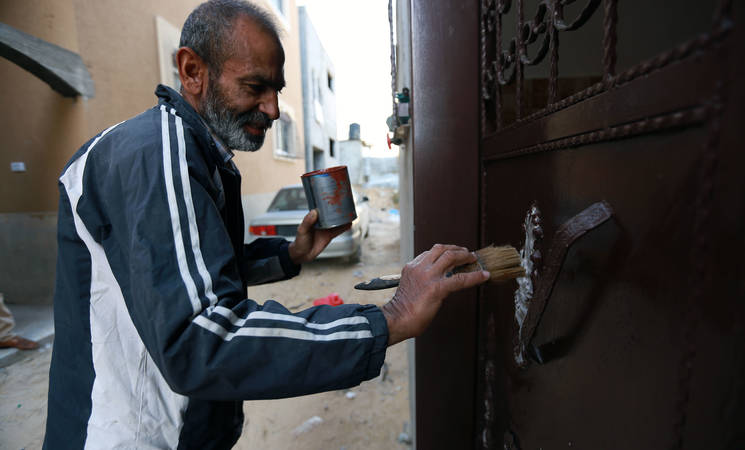Shukri Ali is painting the door of his newly reconstructed house. Shukri's family completed the reconstruction of their house with support from UNRWA. © 2016 UNRWA Photo by Rushdi Al-Sarraj