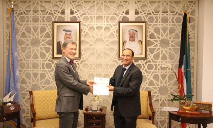 Kuwait's Ambassador to the United Nations in New York, Mr. Al-Otaibi (right), hands over a cheque of the contribution amount to UNRWA Representative in New York, Peter Mulrean (left). Photo courtesy of the Permanent Mission of the State of Kuwait to the United Nations