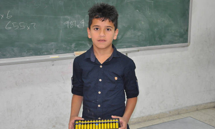 Noor Eideen with his hand abacus in his classroom. © 2018 UNRWA Photo by Riham Jafary