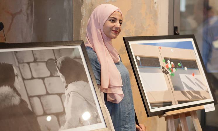 طلاب من لاجئي فلسطين من سوريا يعرضون أعمالهم © صورة للأونروا بعدسة جيسي ثومبسون