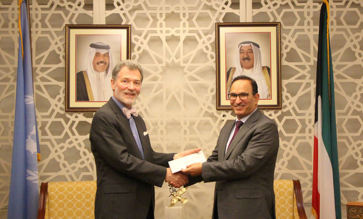 The Permanent Representative of the State of Kuwait and Ambassador to the UN, H.E. Mr. Mansour Al-Otaibi, hands a cheque to Mr. Peter Mulrean, Director of the UNRWA Representative Office in New York.