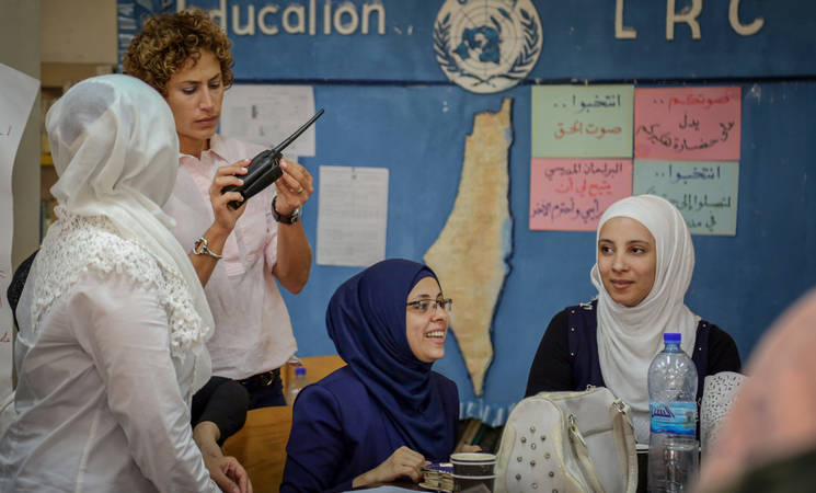 Elsie Abdallah adjusts the radio frequency as participants learn the phonetic alphabet © 2018 UNRWA Photo by Ahmad Abu Zeid.