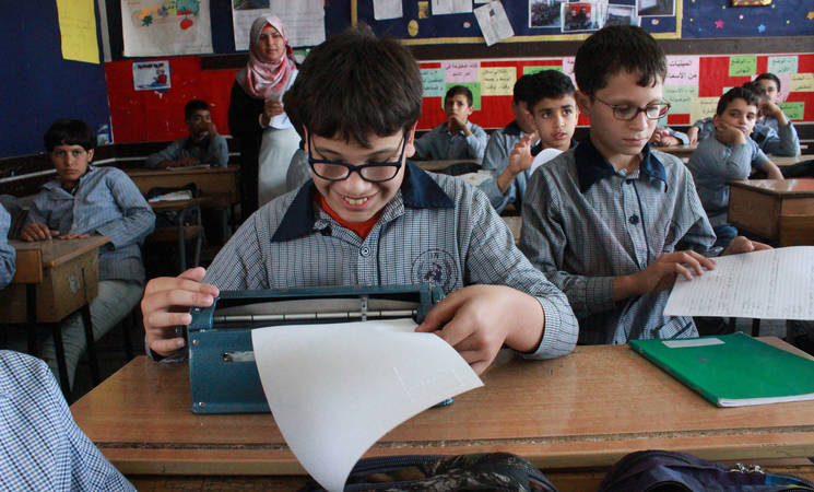 UNRWA student in Lebanon, Khaled Safouri behind his Braille book at class.© 2019 UNRWA Photo by Abeer Noof