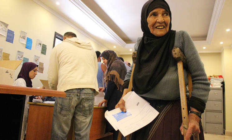 A Palestine refugee beneficiary collects UNRWA cash assistance provided by the Agency's Social Safety Net programme. 2019 UNRWA Photo by Maysoun Mustafa
