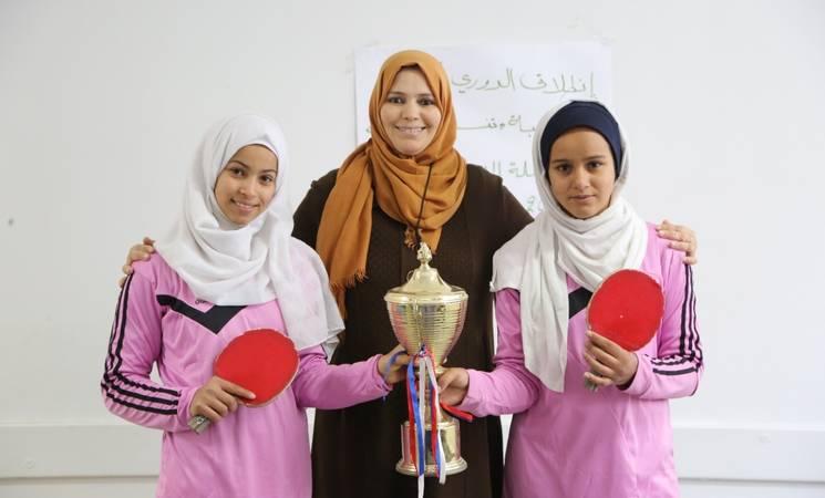 تحمل السيدة فاطمة قشا (في الوسط) مع رحمة معمر (يمين) وزميلتها منى (يسار) كأس الفوز بدورة تنس الطاولة في المدرسة. الحقوق محفوظة للأونروا ، 2019 ، تصوير خليل عدوان.