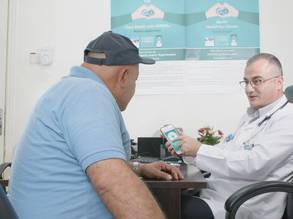 """A doctor at Al-Nuzha health centre in Amman, Jordan explaining to a patient with a non-communicable disease (NCD) about how to use the newly released NCD smart phone application """"Your health with UNRWA"""" and how it connects to her electronic health record in UNRWA e-Health system.  © 2020 UNRWA Photo by George Awwad"""