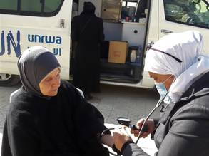 Ninety-year-old Kadraa al-Mawed (left), a returnee to the Yarmouk Palestine refugee camp on the outskirts of Damascus, receives some medical attention from an UNRWA medical worker at the UNRWA Mobile Clinic. © 2020 UNRWA Photo