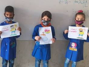 Palestine refugee children from the UNRWA Mikhael Kashour school in Aleppo show off their art from the COVID-19 activity they participated in, designed to raise awareness about the virus and teach children how to adapt to the new situation. © 2020 UNRWA Photo