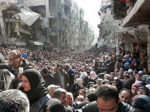 Thousands of residents of Yarmouk Palestine refugee camp in Syria line up to receive humanitarian aid after UNRWA regains access to the camp in January 2014, providing a limited quantity of food and hygiene items at a distribution area inside the camp. © 2014 UNRWA Photo