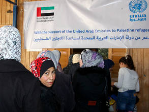 Palestine refugees from Damascus queue at UNRWA's Alliance Distribution Center to receive food packages, made possible by the generous funding of the United Arab Emirates (UAE). Damascus, November 2014. © UNRWA Photo by Taghrid Mohammad.