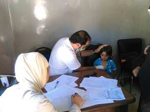 An UNRWA doctor examines a young child in Yalda, August, 2015 ©UNRWA