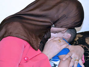 منى تحتضن طفلها الصغير بعد عملية جراحية ناجحة لعلاج نوبات الصرع المتكررة. صورة مقدمة من مبادرة تعاون