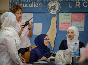 تقوم إلسي عبدالله  بتعديل تردد الراديو بينما تتعلم المشاركات الحروف الأبجدية الصوتية © 2018 صورة للأونروا، أحمد أبوزيد