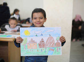 "One of the students during the ""Peace with Japan Art Contest"" at the Gaza Training Centre presenting his drawing © 2019 UNRWA Photo by Ibraheem Abu Usheeba"