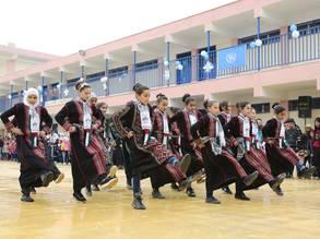 طلاب لاجئين من فلسطين يؤدون رقصة فلكلورية خلال حفل افتتاح مدرستهم الجديدة في مخيم درعا للاجئين، سوريا.  (©) 2020 صور الأونروا