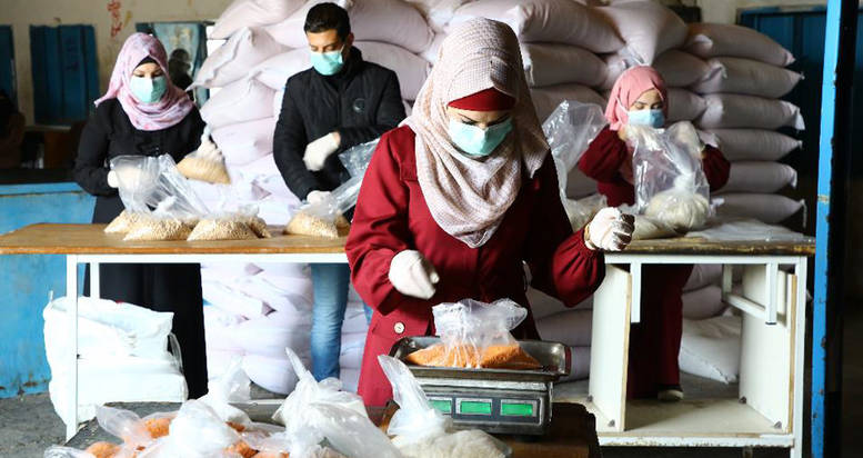 Palestine refugees, employed through the UNRWA Cash-for-Work programme, pack food items at the UNRWA Beach Distribution Centre in Gaza during the COVID-19 emergency. © 2020 UNRWA photo by Khalil Adwan