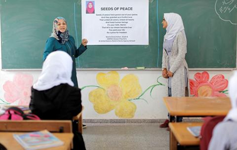 """أماني كُلاب (إلى اليسار) معلمة حقوق الإنسان وبسمة عصفور (إلى اليمين) تشرح ضمن حصة دراسية في مدرسة عبسان الإعدادية للبنات، جنوب قطاع غزة، القصيدة الفائزة في مسابقة رسائل السلام الملهمة 2017 بعنوان """"بذور السلام"""". جميع الحقوق محفوظة: الأونروا غزة 2017، تصوير"""