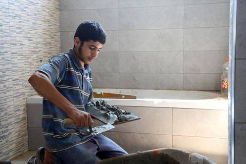 Palestine refugee Abed Al-Rahim during his work in tiling. © 2018 UNRWA Photo by Khalil Adwan