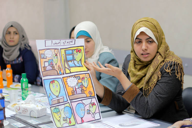 19-year-old Sarah Al Ramlawi explaining her drawings to Swiss cartoonists during a meeting in a Community-Based Organization in Gaza city. © 2017 UNRWA Photo by Rushdi Al-Sarraj