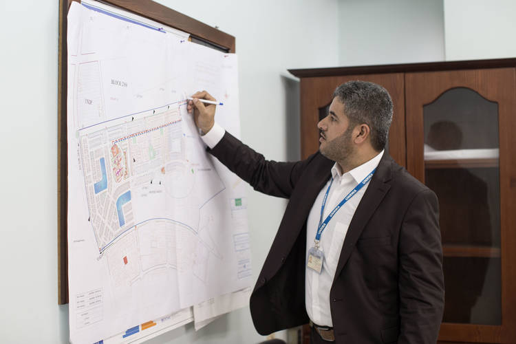 Gender Champion Award winner and acting deputy chief of the Infrastructure and Camp Improvement Programme, Muin Moqat, is explaining the importance of the co-signing practice in the third phase of the Rafah Rehousing Project in southern Gaza. © 2017 UNRWA