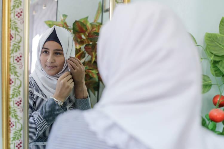 سجود طه البالغة من العمر أربعة عشر عاماً تحاول ترتيب حجابها في مدرسة النصيرات الإعدادية للبنات (أ)، وسط قطاع غزة. جميع الحقوق محفوظة: الأونروا غزة 2017، تصوير تامر حمام