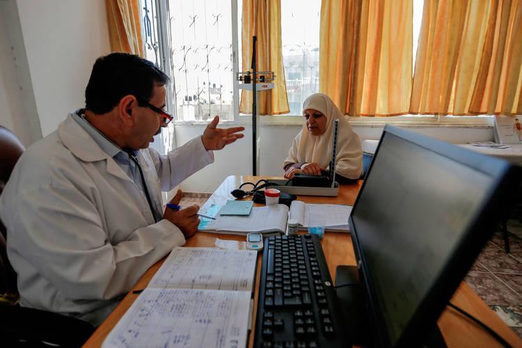 Nurse Waleed Omar (left) discusses her lab blood test result with Kamla Nassar in the UNRWA Beach Camp Health Centre, western Gaza. © 2017 UNRWA Photo by Rushdi Al-Sarraj