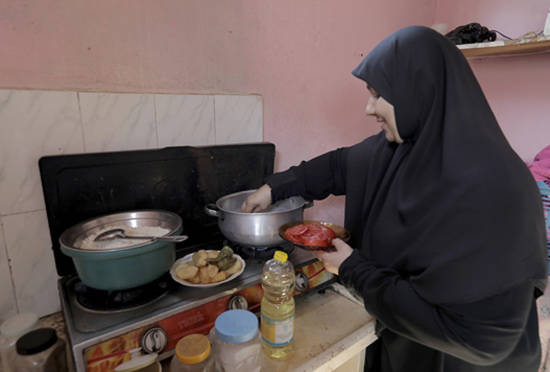Nisreen Foad Qasem preparing Maqloba (Palestinian dish) for lunch using the cooking oil and rice she receives as part of the UNRWA food basket. © 2018 UNRWA Photo by Mohammad Al Hinnawi