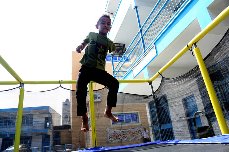Twelve-year-old Omer Abu Dlaj, who lost his arm in the 2008 hostilities in Gaza, jumps on a trampoline during the Summer Fun Weeks (SFWs) at Al-Fakhora Preparatory Boys School A in northern Gaza. © 2016 UNRWA Photo by Hiba Kreizim