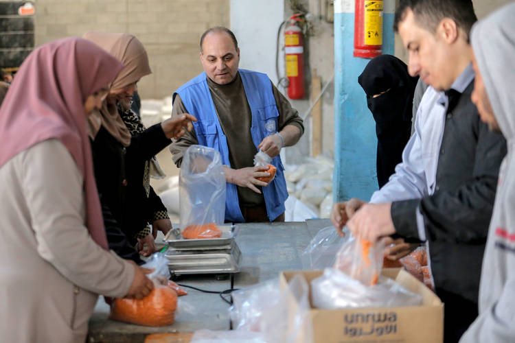 Rabea Abu-Tabeakh (middle), an UNRWA Distribution Officer, managing co-workers packing food parcels in Al-Touffah Distribution Centre, eastern Gaza.  © 2017 UNRWA Photo by Rushdi Al-Sarraj