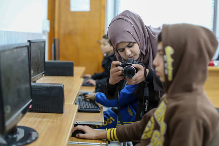 20-year-old Ala'a Abu Al-Ajeen, a Job Creation Programme (JCP) beneficiary, taking a photo of a group of children at the Deir El-Balah Rehabilitation Association in central Gaza. © 2017 UNRWA Photo by Rushdi Al-Saraj