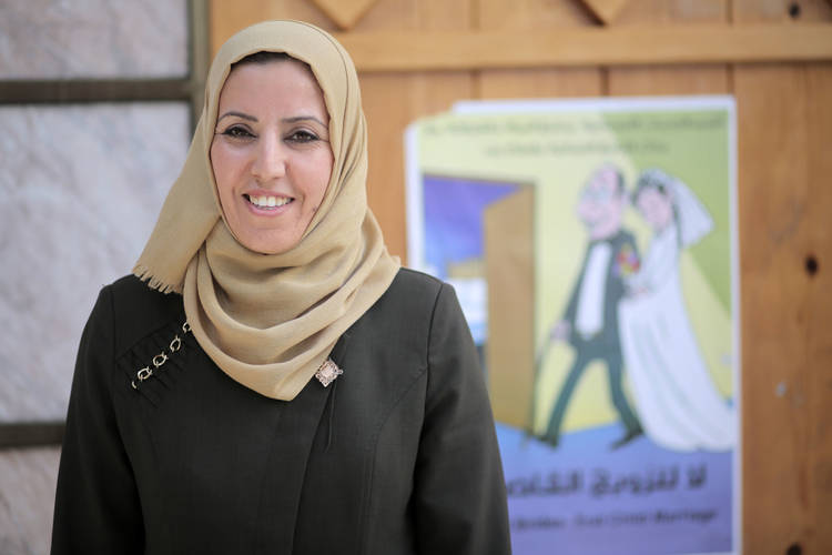 "Lawyer Hayat Mahmoud standing in front of a poster distributed during the ""Girls not Brides, End Child Marriage"" initiative in Al-Daraj Women's Programme Centre in Gaza city. Photo credit: ©UNRWA Gaza 2017. Photo by Rushdi Al-Saraj."