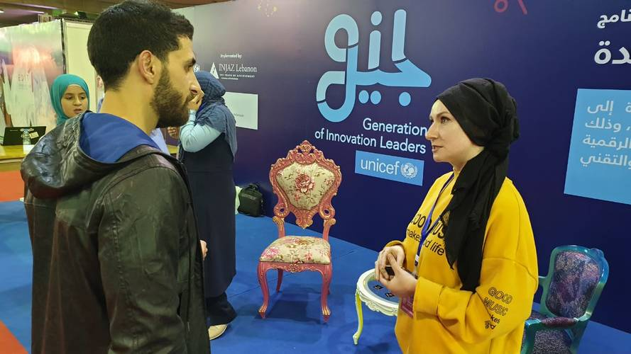 """Rasha Yassine, right) speaks to a visitor during an exhibition of the """"Generation of Innovation Leaders"""" project in Lebanon. © 2019 UNRWA Photo"""