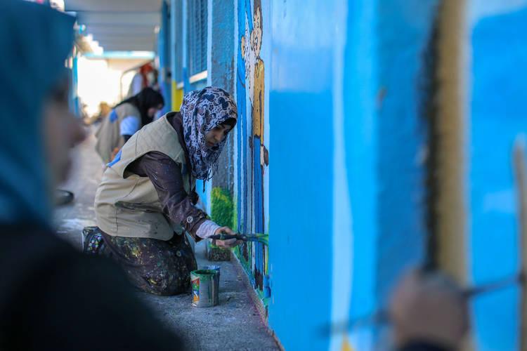 Artist Eman Abu Saqqer is drawing on the walls of the UNRWA Preparatory Boys School in Gaza. © 2016 UNRWA Photo by Rushdi Al Sarraj
