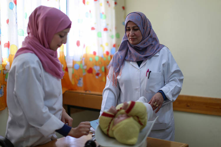 52-year-old Amal Al-Jaish (right) follows up with the practical nurse Noor Afana (left) while she is weighing a baby before giving it an inoculation in the Saftawi Health Centre in northern Gaza. © 2017 UNRWA Photo by Rushdi Al-Saraj