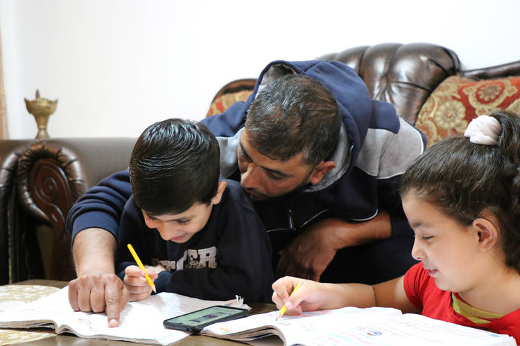 Mohammad Lutfi helps his children Ahmad and Dalia do their homework sent to them via Facebook by their teachers from the UNRWA boy's and girl's school in Aida Camp. © 2020 UNRWA Photo by Yumna Patel