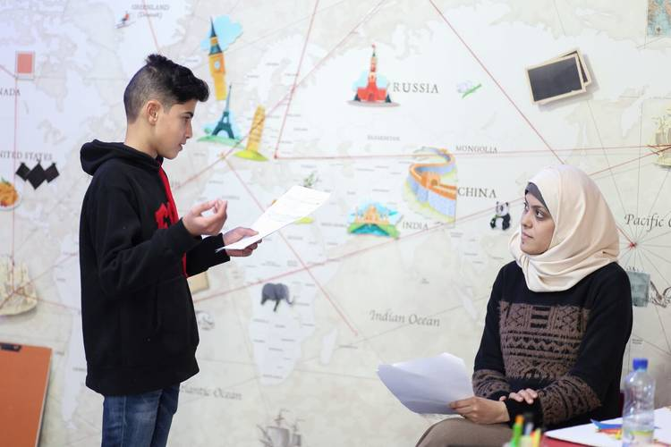 11-year old Qais Atallah, one of 16 child actors of the second educational programme season on UNRWA TV, and 33-year old Amal Hmaid, one of the producers of the UNRWA TV EiE project, discuss the script at UNRWA TV studio. ©2018 UNRWA Photo by Tamer Hamam.