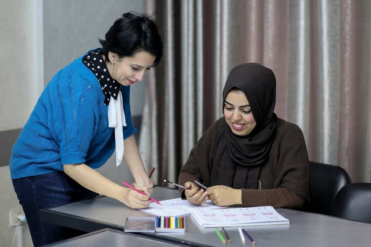 Artist Majdal Nateel (left) and Kholoud Al-Dali (right), a participant in the comic-drawing training organized by UNRWA's Communications with Communities team at a community-based organization in Gaza City. © 2018 UNRWA Photo by Rushdi Al-Saraj.