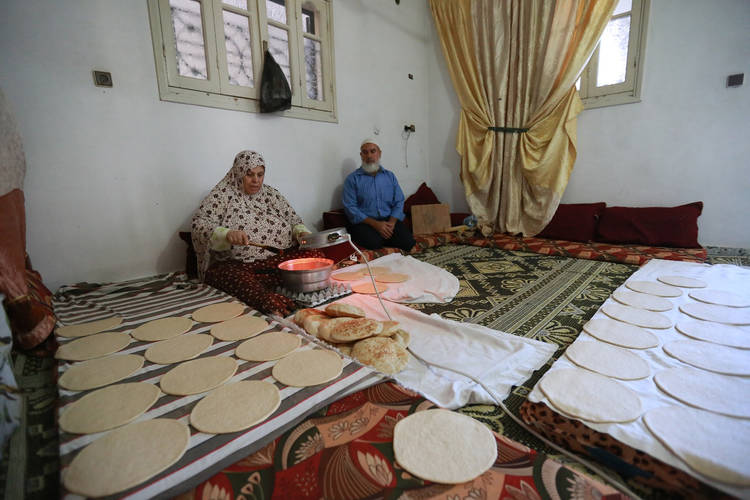 Kulthoom Baroud is baking bread together with her husband Husein in their rented home in the Zaitoun area in eastern Gaza City. © 2016 UNRWA Photo by Rushdi al-Sarraj