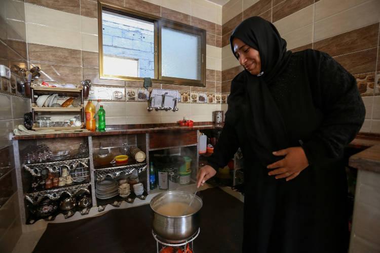 Etimad al-Ejla is cooking lunch in her newly reconstructed home in Shujaiya, in eastern Gaza City. © 2016 UNRWA Photo by Rushdi al-Sarraj