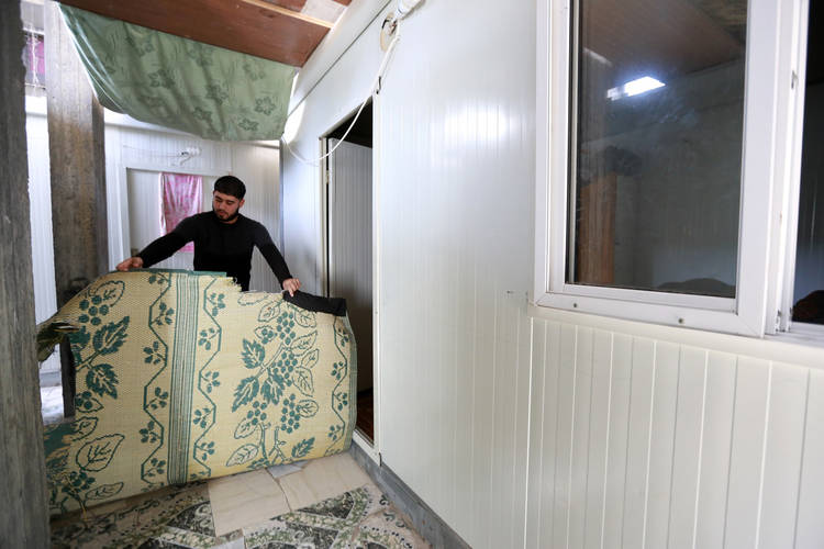 Saleh Swidan inside the container where he, his wife and their two children have lived for two years. © 2016 UNRWA Photo by Rushdi al-Sarraj