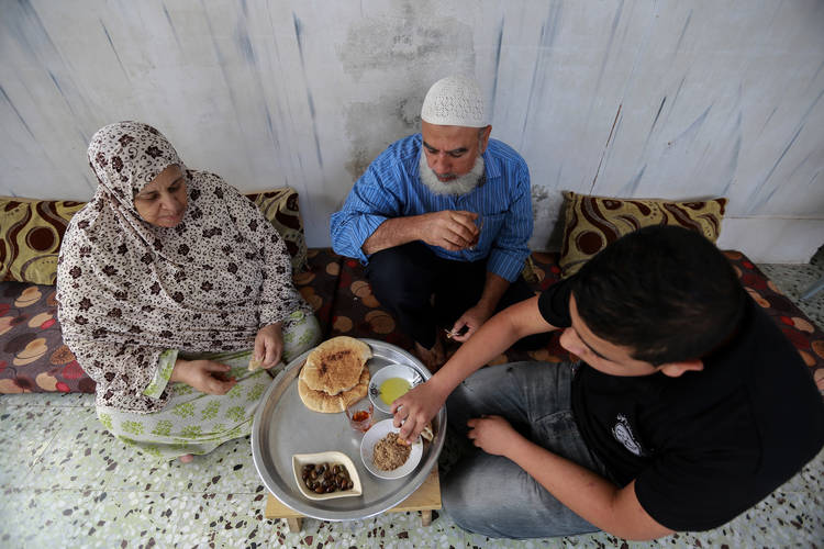 Husein Abu-Al-Lil (middle) is having breakfast with his wife, Kulthoom, and their son in their rented home in the Zaitoun area in eastern Gaza City. © 2016 UNRWA Photo by Rushdi al-Sarraj