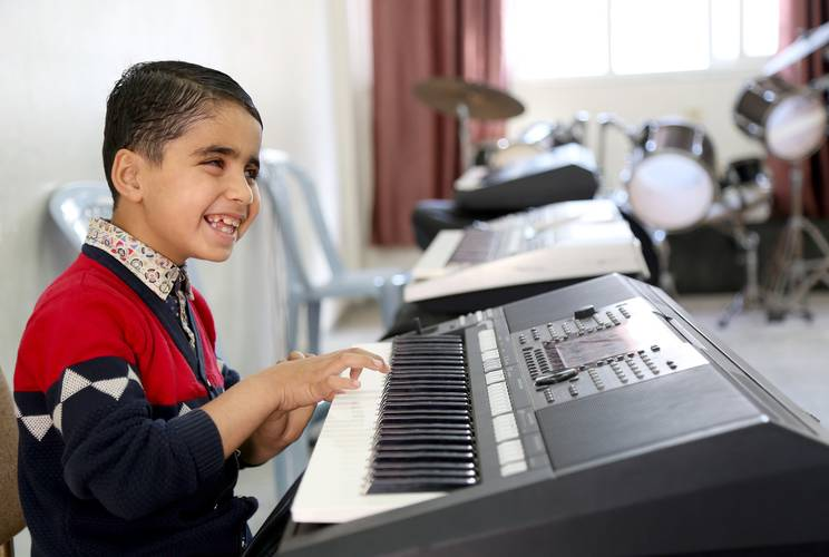 Mohammed Alwan, who was born blind, playing the electronic piano in the music class at the UNRWA Rehabilitation Centre for Visually Impaired (RCVI) in Gaza. © 2018 UNRWA Photo by Khalil Adwan.
