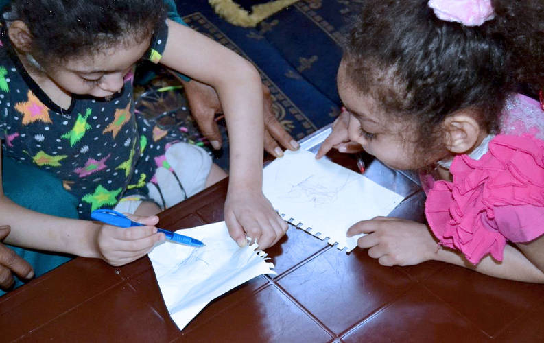 Nourhane and Malak enjoy drawing pictures together following successful surgery to prevent recurrent epileptic seizures. Photo courtesy of Taawon