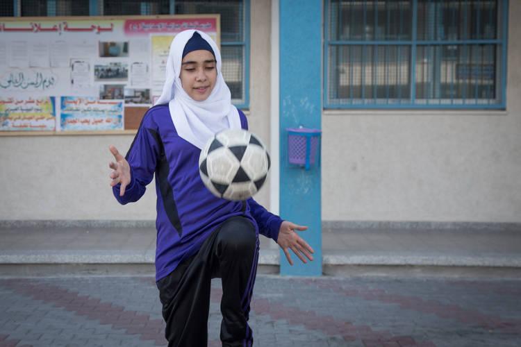 Toqa Al-Zayan, a 13-year-old Palestine refugee, playing football in UNRWA Jabalia Preparatory Girls School C, Jabalia camp, northern Gaza Strip. © 2017 UNRWA Photo by Tamer Hamam