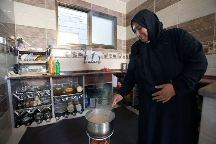 Etimad al-Ejla is cooking lunch in her newly reconstructed home in Shujaiya, in eastern Gaza City. © 2016 UNRWA Photo by Rushdi al-Sarraj