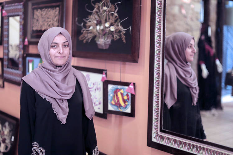 24-year-old Soad Hadido, a participant in the Gender Initiative's Social and Recreational Spaces for Women and Girls project, presents a mirror she embroidered at an exhibition organized by the Gender Initiative. © 2017 UNRWA Photo by Hussein Jaber